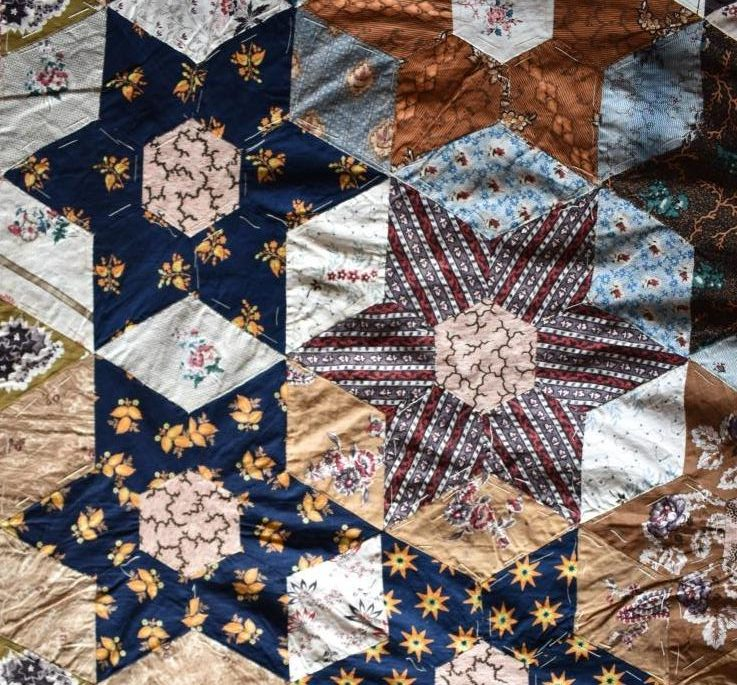 Coloured patchwork stars in quilt top.