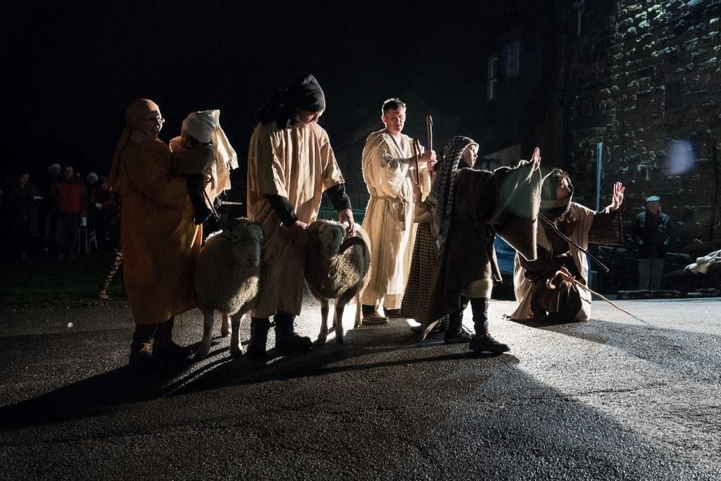 People dressed as shepherds, in semi-darkness