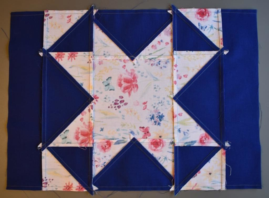Blue border on patchwork star with seams pressed towards border