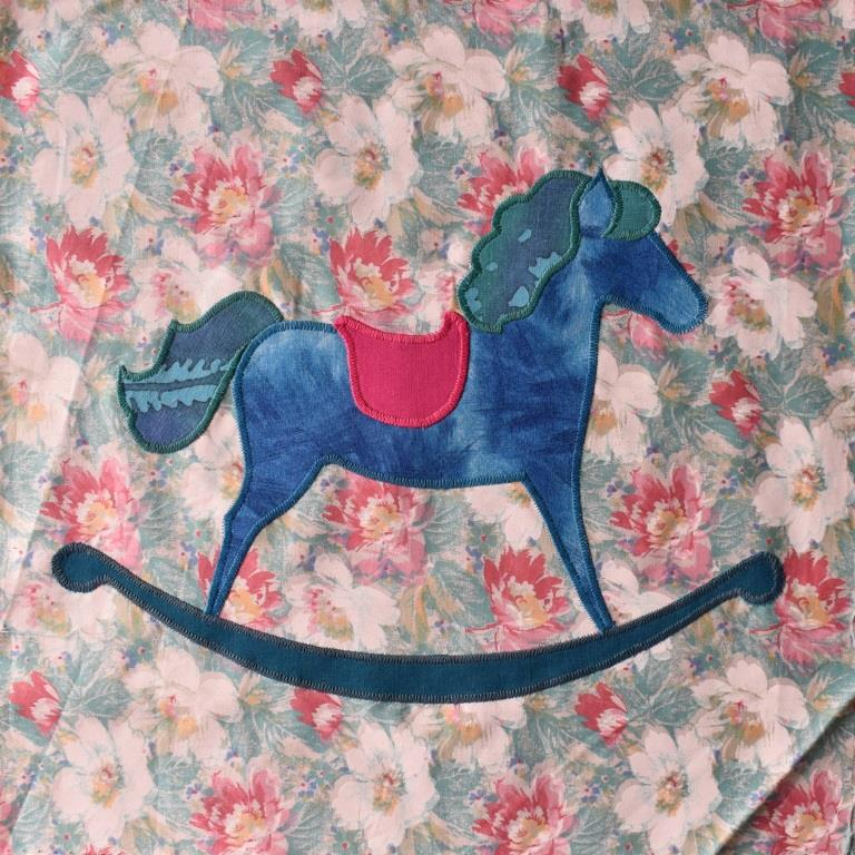 Blue rocking horse appliques onto floral background