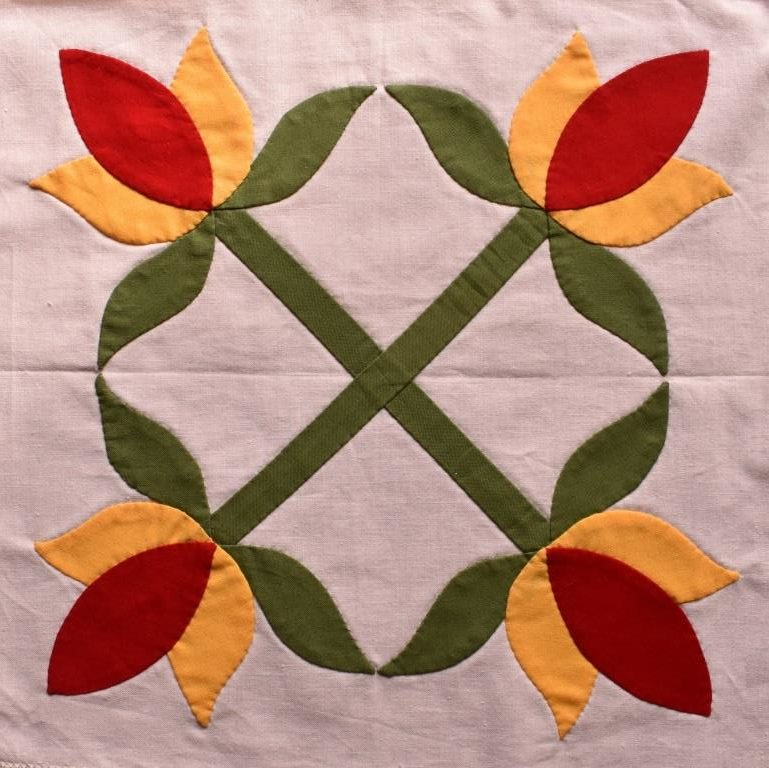 Stylized four-fold symmetrical design of red & yellow tulips with green leaves