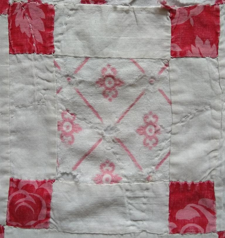 Nine-patch patchwork block with larger pink printed centre