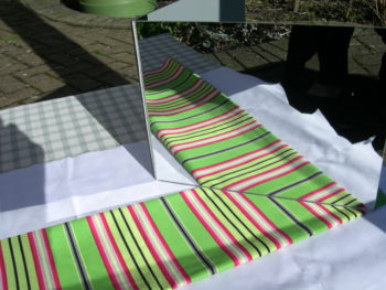 Mirrow set to show refelection of striped fabric around a corner